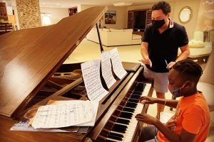 Scott Cohen teaching piano lessons to his student